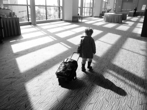 Little girl carrying her suitcase